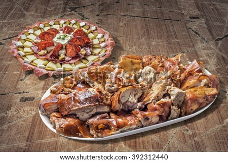 Plateful of Spit Roasted Pork Slices and Serbian Traditional Appetizer Meze Set on Old Cracked Peeled Wood Surface - stock photo