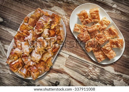 Platefuls of Cheese Pie Gibanica and Spit Roasted Pork Slices, Placed on Old, Lacquered, Weathered, Cracked, Peeled-off Old Wooden Garden Table Surface.