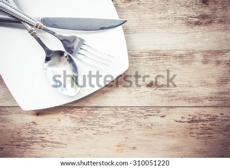 Plates and cutlery on a wooden table - stock photo