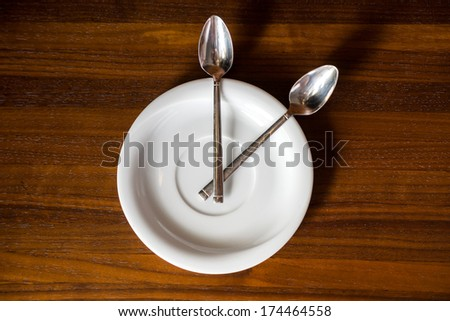 Plates and spoons look like a clock - stock photo