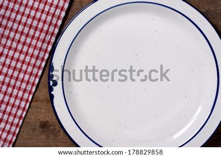 Plates and table cloth on wooden table with copy space - stock photo