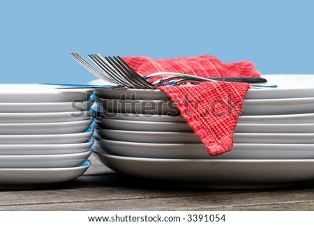 plates, cutlery, & napkins in a stack - isolated on blue