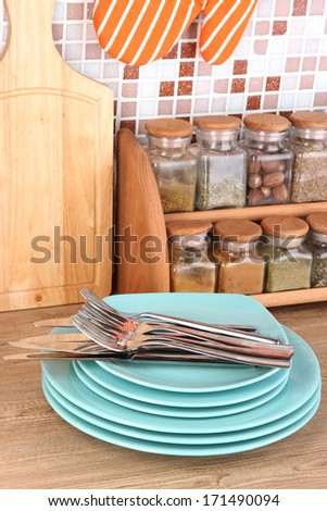 Plates in kitchen on table on mosaic tiles background - stock photo