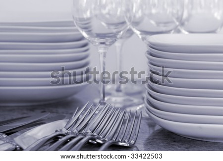 plates, wineglasses, cutlery for home entertaining - stock photo