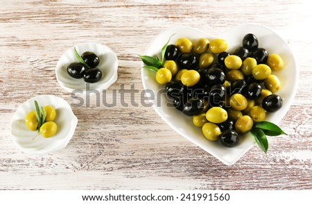 Plates with black and green olives on painted wooden background - stock photo