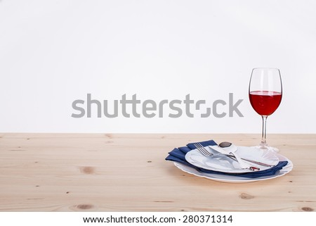 plates with cutlery and wine glass on wooden table - stock photo
