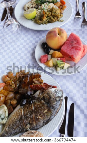 Plates with different dishes. Fruits, seafood, garnish.
