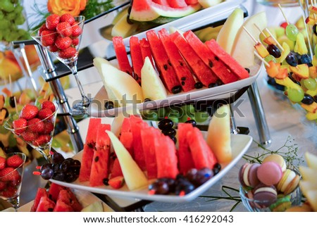 Plates with different type of fruits: grapes, strawberries, pineapple, watermelon, apricots