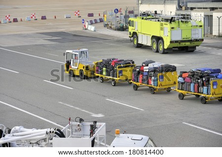 Platform at airport with fire engine and luggage of passengers that is transported by a small trailer - stock photo