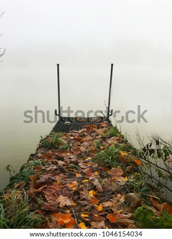 Platform on a river in fog with autumn leaves