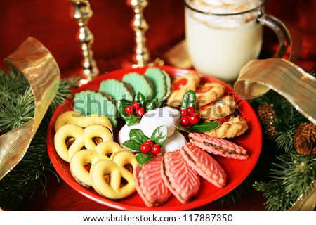 Platter of colorful christmas cookies with eggnog and christmas decorations.  Shallow depth of field with focus on center of cookies. - stock photo
