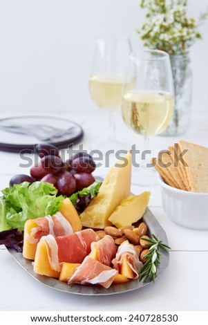 Platter of gourmet party food, gruyere cheddar cheese with prosciutto parma ham wrapped rockmelon served with white wine - stock photo