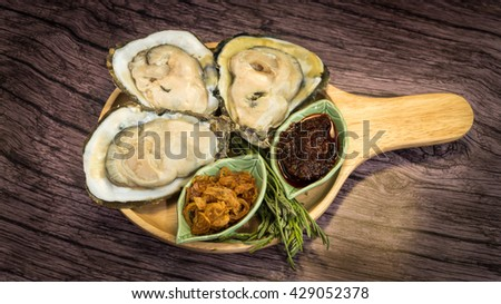Platter of oyster on wood plate.with spicy sauce seafood, health and wellness related concepts - stock photo