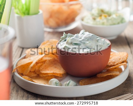 Platter of potato chips and fresh vegetables with dip, selective focus - stock photo