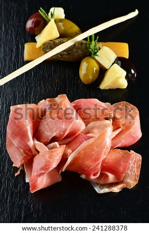 Platter of serrano jamon/Prosciutto and olives pate  - stock photo