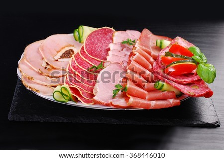 platter of sliced ham,salami and cured meat with vegetable decoration on black table - stock photo