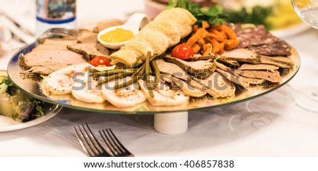 platter of sliced ham,salami and cured meat with vegetable decoration on festive table. - stock photo