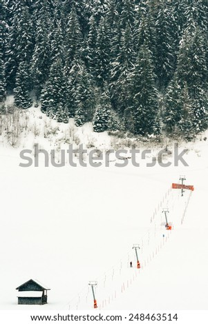 Platter ski lift at beginners piste pulling a skier up the flat slope for his first tries during snowfall - stock photo