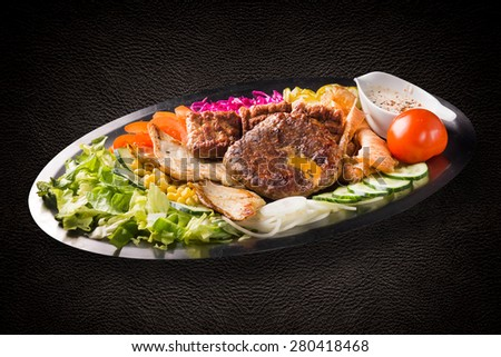 Platter with grilled meat, cheese, chicken, cevapi and salad on dark background - stock photo