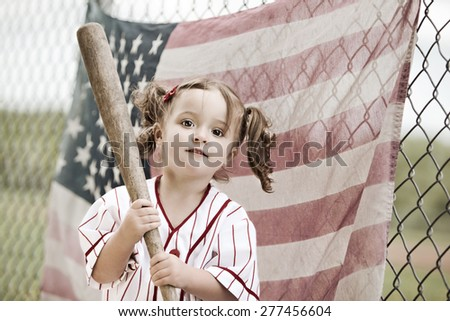 Play Ball!  Adorable toddler wearing a vintage baseball uniform and holding a baseball bat.  A faded American flag hanging from a chain link fence in the background.  - stock photo