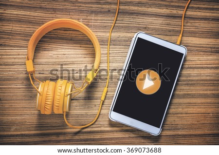 Play button on tablet with headphones on wooden table - stock photo