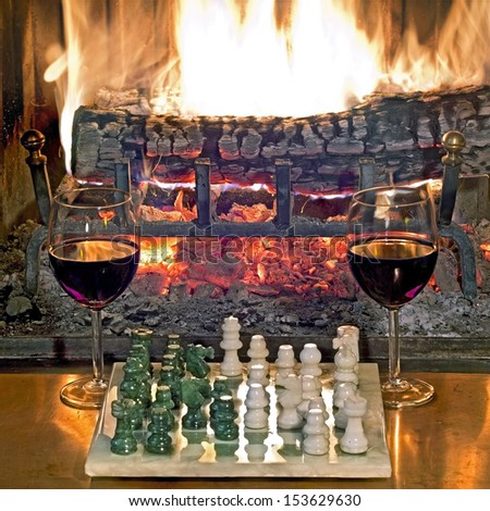 play chess drinking red wine in front of a roaring fireplace - stock photo