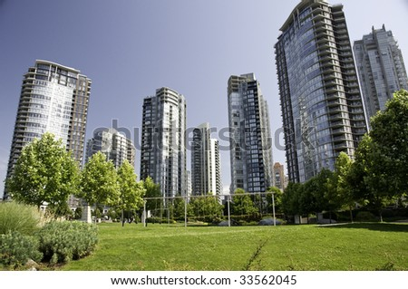 Play ground between large highrise towers on a beautifull sunny day. - stock photo