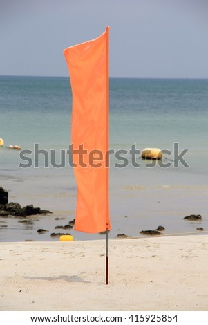 Play it Safe, Beach warning flag flapping in the wind, It is reccomended not to go in the water under red flag conditions. - stock photo