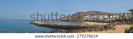 PLAYA BLANCA, LANZAROTE, SPAIN - MAY 10, 2015: Panorama of the western end of Playa Blanca promenade with holiday makers on the man made Flamingo beach and the lighthouse.
