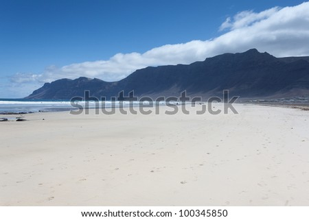 Playa De Famara is a popular beach for surfers on the island of Lanzarote. - stock photo