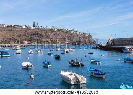 PLAYA DE SANTIAGO, LA GOMERA, SPAIN - FEBRUARY 13. Fishing boats in the port of Playa de Santiago on February 13, 2016. The village is in the south of the island. On top of the rock the tourist resort - stock photo