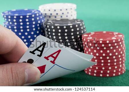 Player betting stacks of chips with pair of ace on hand. - stock photo