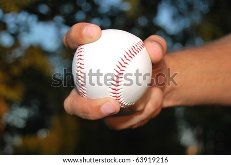 Player Gripping a New Baseball and throws the ball on defense - stock photo
