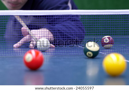 Player is preparing to make the hit overcoming the ping-pong net. the billiard with snooker balls is played on ping-pong table. Selective focus on white ball. - stock photo