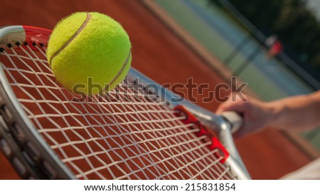 Player's Hand With Tennis Racket And Tennis Ball On It - stock photo