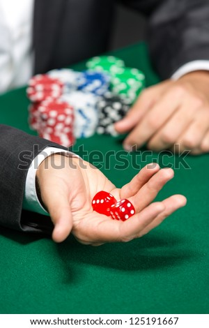 Player throws dices on the poker table. Risky entertainment of gambling