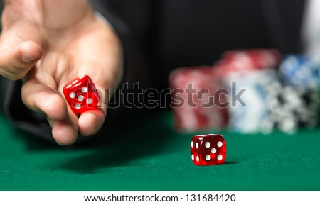 Player throws dices on the poker table. Symbol of addiction to the poker - stock photo