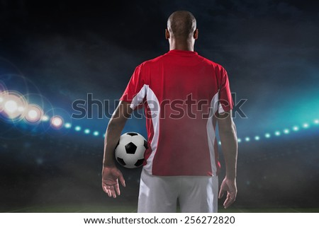 Player with a soccer ball on the field, rear view - stock photo