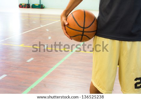 Player with basketball ball in gym - stock photo