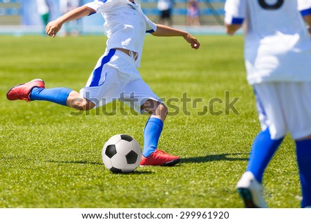 players playing football soccer game. Running players in blue and yellow uniforms - stock photo