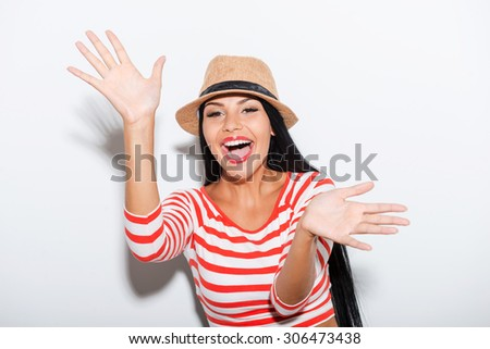 Playful and carefree. Playful young woman stretching out her hands while standing against white background - stock photo