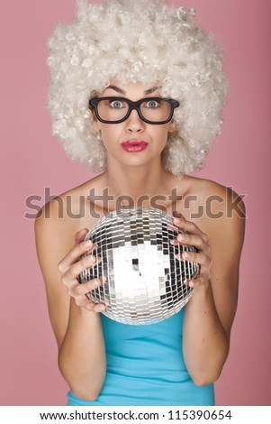 Playful and funny woman wearing a curly wig on a pink background. Having fun. - stock photo