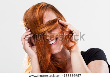 Playful and happy young redhead woman smiling and being shy covering her eyes with the hair