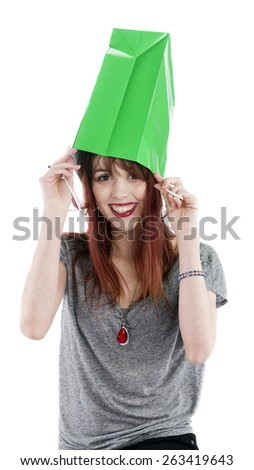 Playful and Smiling Young Teenage Woman with Green Shopping Bag on Head in front of White Background