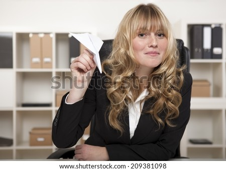Playful attractive young blond businesswoman with a paper plane in her hand, sitting at her desk ready to launch it at a colleague. - stock photo