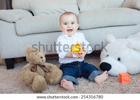 Playful baby boy with toys - stock photo