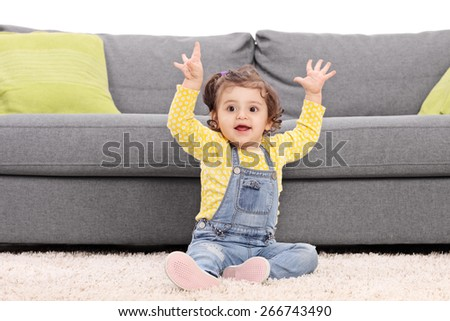 Playful baby girl sitting on the floor next to a modern sofa and gesturing happiness isolated on white background - stock photo