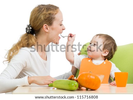 playful baby spoon feeding his mother isolated on white - stock photo