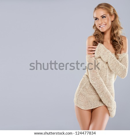 Playful beautiful blonde model laughing as she wraps her arms around the skimpy trendy off the shoulder top that she is wearing - stock photo