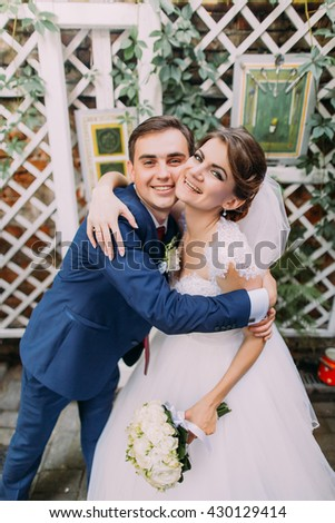 Playful beautiful bride and groom embracing at their wedding day. Close-up - stock photo